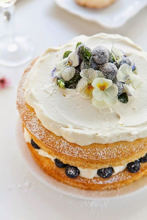 a naked wedding cake with whipped cream, sugared berries and blooms for summer
