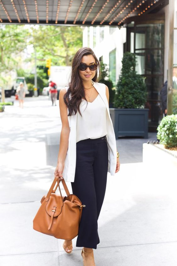 navy culottes, a white top, a white long vest, sandals and a large brown bag