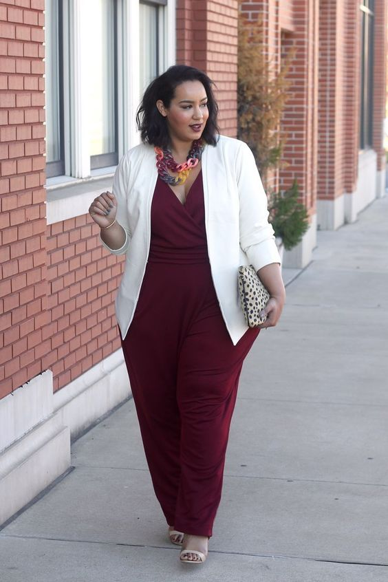 a burgundy jumpsuit with wide pants, a V-neckline, a white jacket and a printed clutch