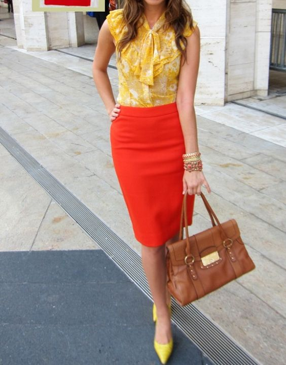a reddish orange skirt, a printed yellow blouse, yellow shoes and a brown bag