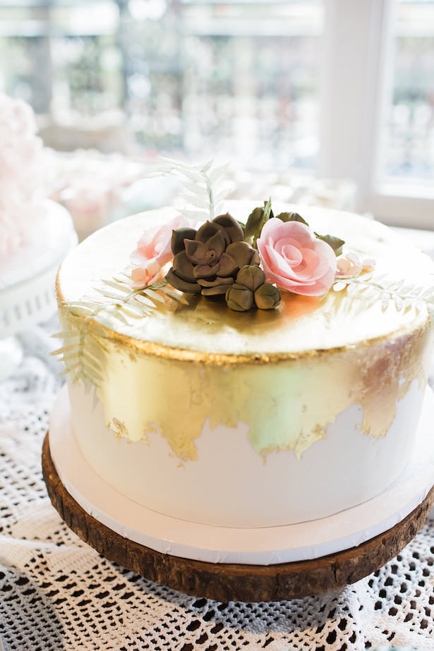 White wedding cake with gold details and flowers and succulents - Brooke Images