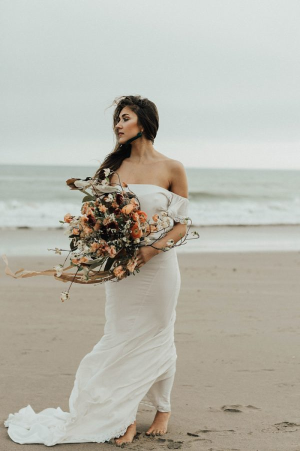 a sheath off the shoulder wedding dress with a small train and lace trim for a fall coastal bride