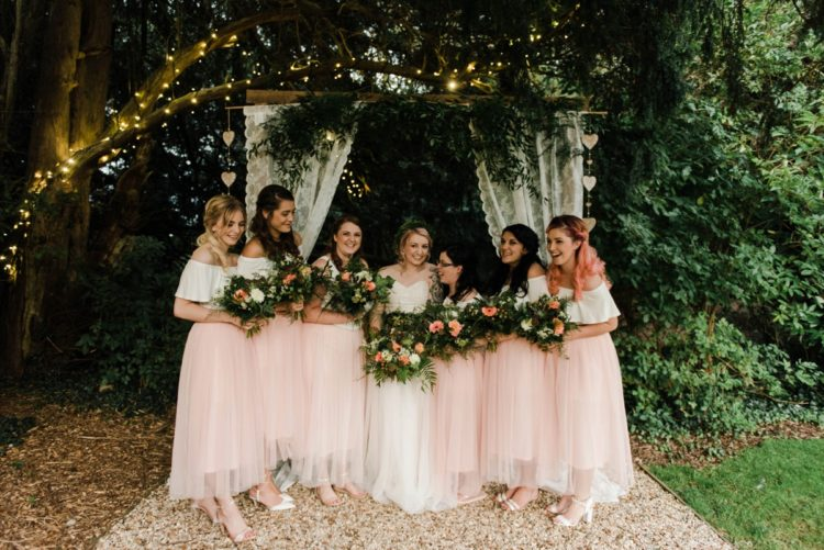 The bridesmaids were wearing white off the shoulder tops and pink tulle midi skirts