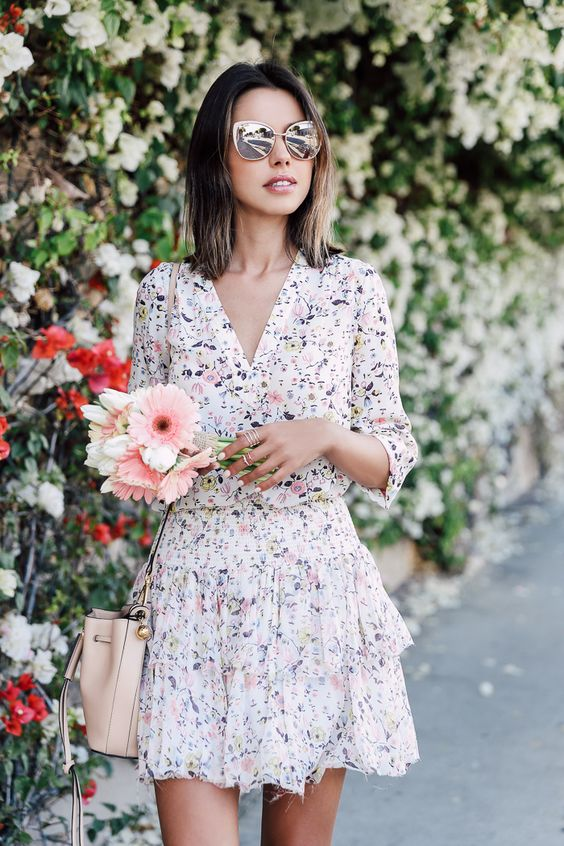 a watercolor floral mini dress with long sleeves and a V-neckline plus a pastel bag