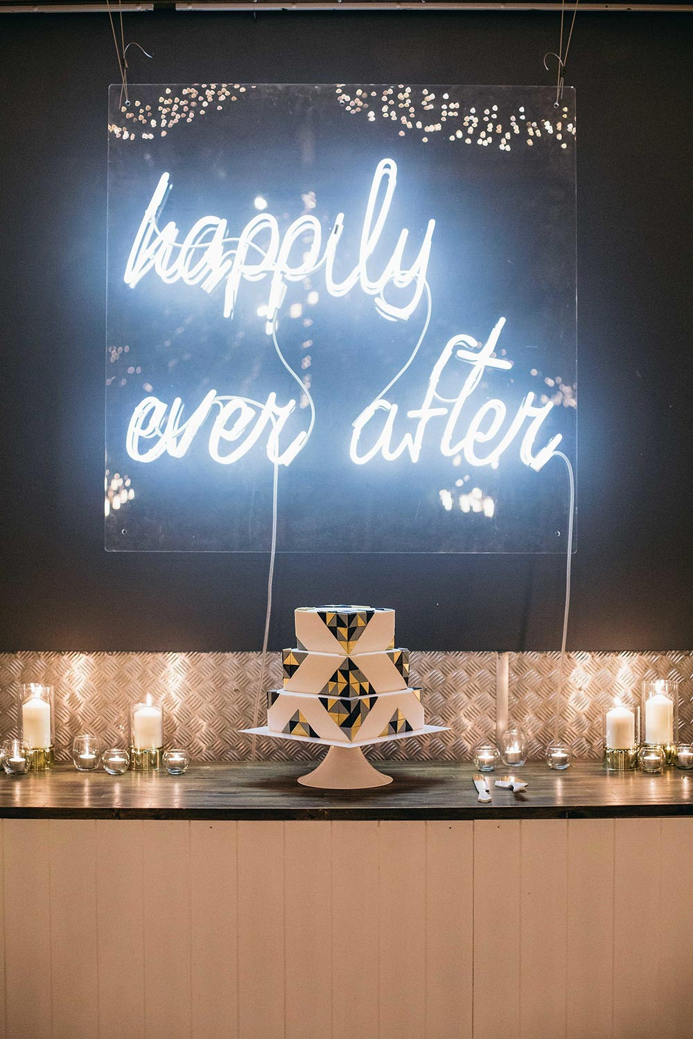 modern square tier wedding cake with geometric black and gold triangles and neon signage
