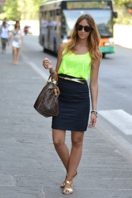 With neon top, pencil skirt, golden flat sandals and printed bag