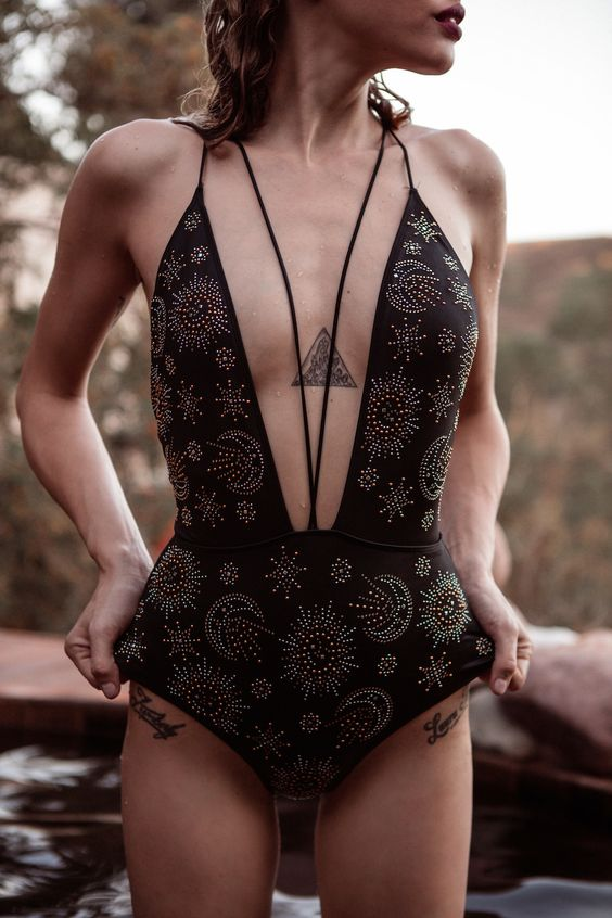 a black printed one piece swimsuit with a plunging neckline highlighted with laces
