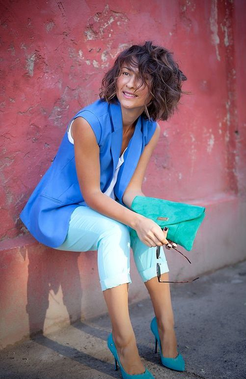 mint cropped pants, a white top, a bold blue vest, turquoise shoes and a clutch