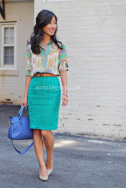 a turquoise skirt, a printed shirt, nude shoes and a bold blue bag