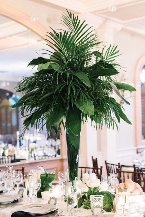 a cool and lush tropical centerpiece of various palm leaves and greenery