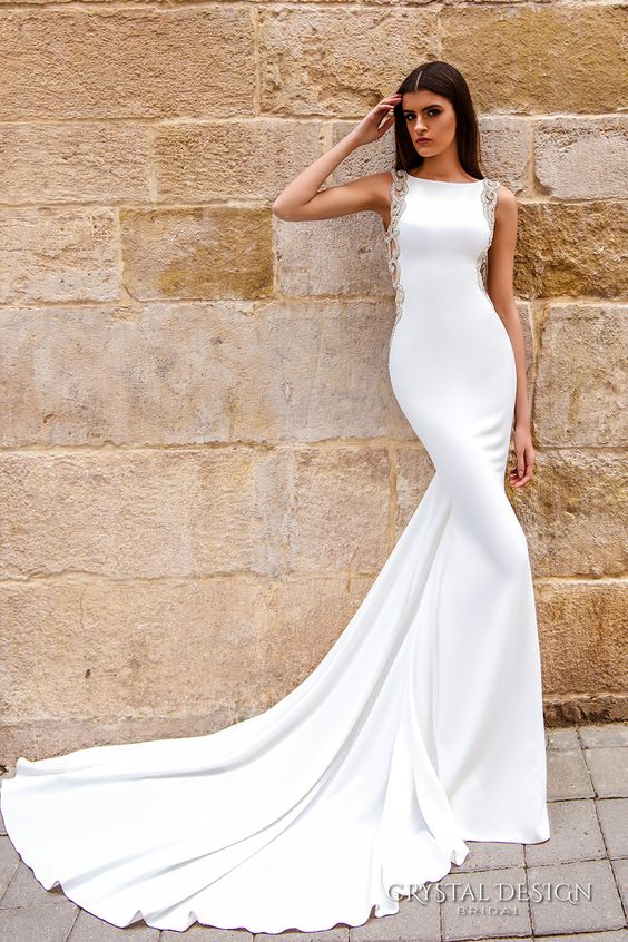 a modern sheath wedding dress with a bateau neckline, embellished sides and a train