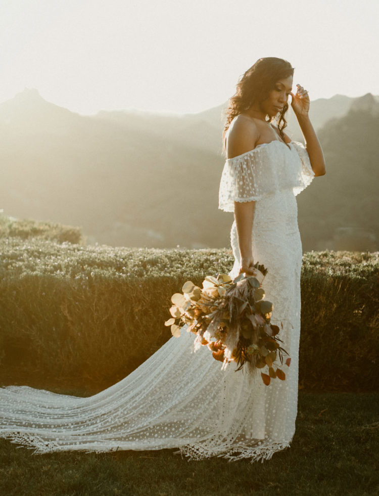 an amazing polka dot off the shoulder sheath wedding gown with a long train and sheer detailing