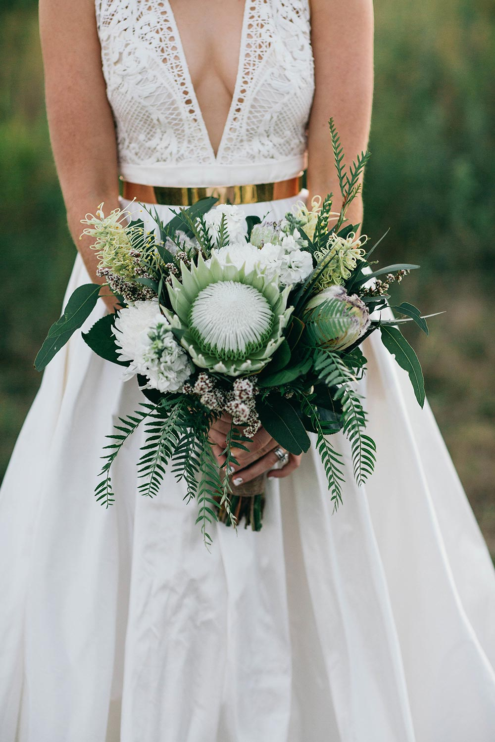 modern bridal bouquet with greenery and proteas