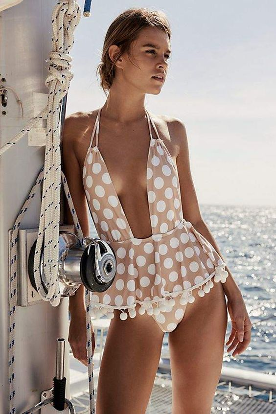 a blush swimsuit with a peplem detail, pompoms, polka dots and a plunging neckline