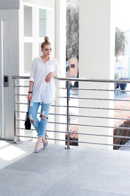 With white loose button down shirt, distressed jeans and black bag