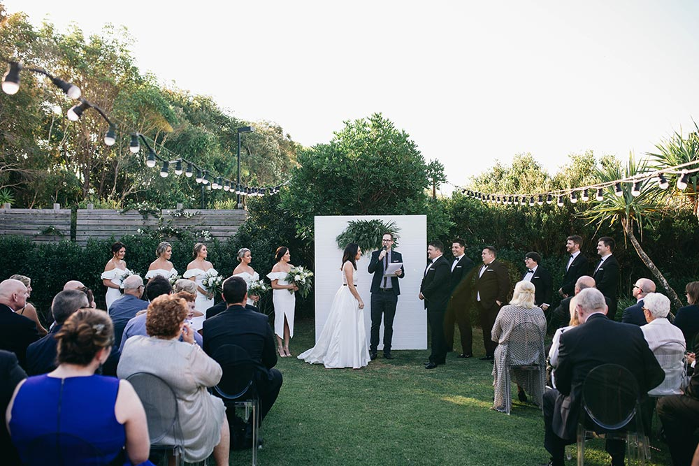 outdoor wedding ceremony with market lights, greenery backdrop and acrylic ghost chairs