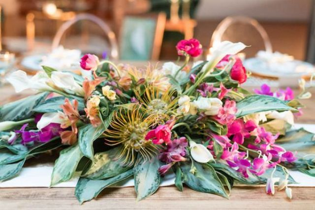 a textural and super lush centerpiece with pink and mauve blooms and greenery looks unusual