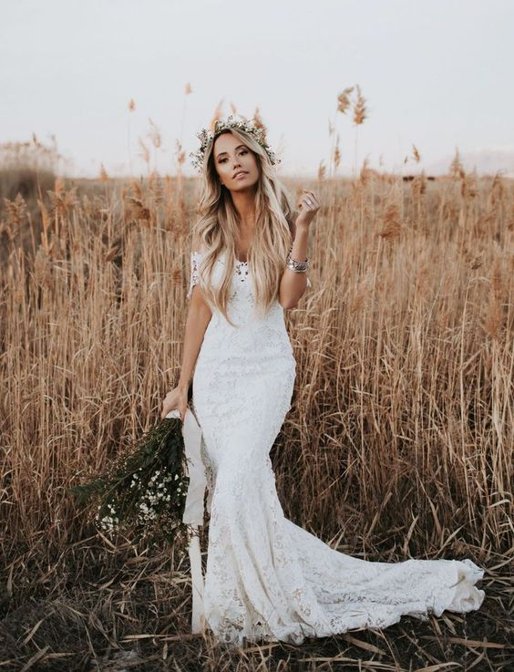 a lace off the shoulder mermaid wedding dress with a small train and a floral crown for a summer boho bride