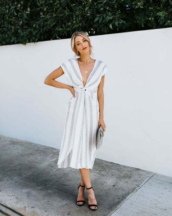 a cute grey and white striped dress with a plunging neckline and cap sleeves, black shoes and a clutch