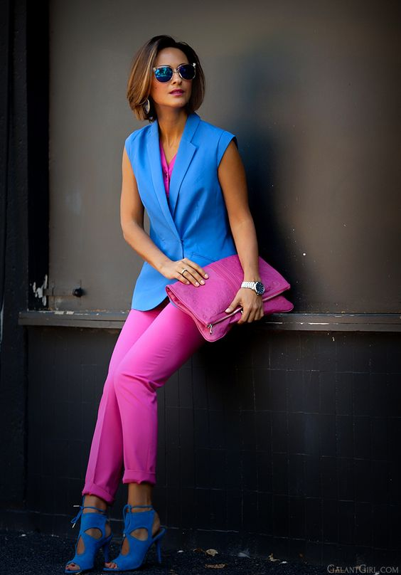 a color block look with a hot pink top, pants and a clutch and bold blue shoes and a vest