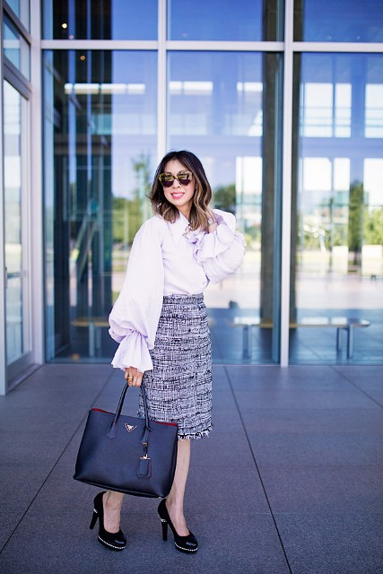 With knee-length skirt, black high heels and black tote