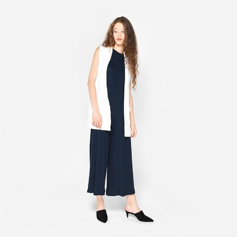 With navy blue jumpsuit and white vest
