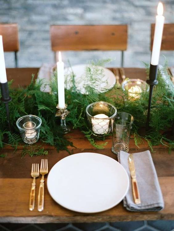 a lush fern table runner with candles is great to rock for a woodland or boho wedding