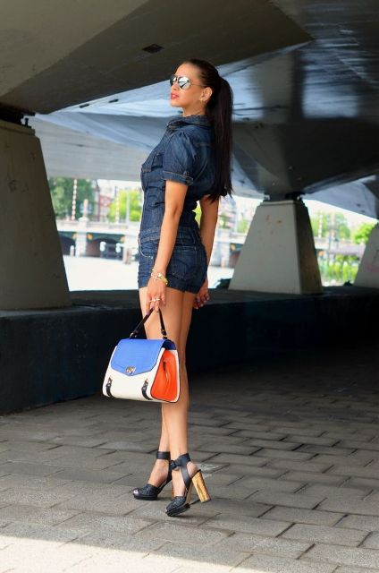 With black high heels and blue, red and white bag