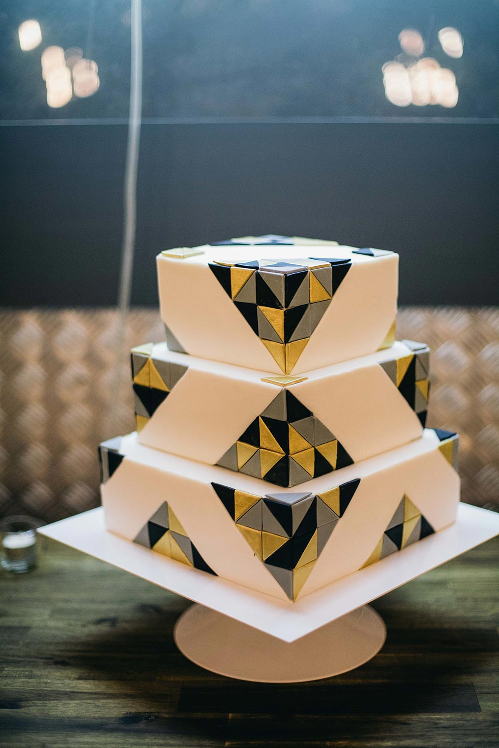 modern square tier wedding cake with geometric black and gold triangles