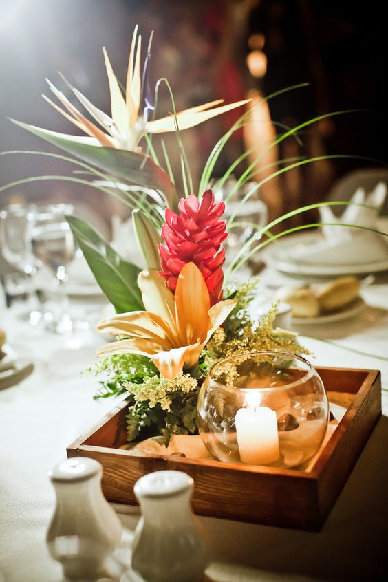 a tropical beach centerpiece with a box of sand, a candle and some tropical blooms