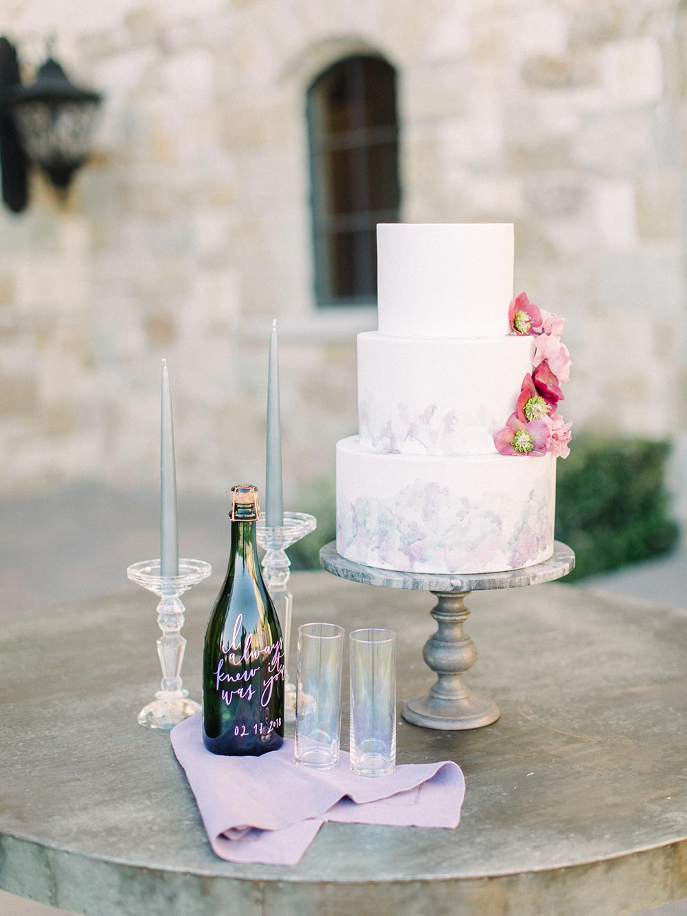 painterly watercolor wedding cake with calligraphed champagne bottle