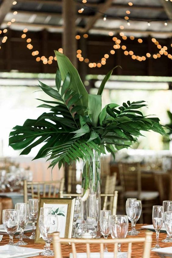a modern tropical leaves wedding centerpiece in a clear glass vase for a cheerful feel
