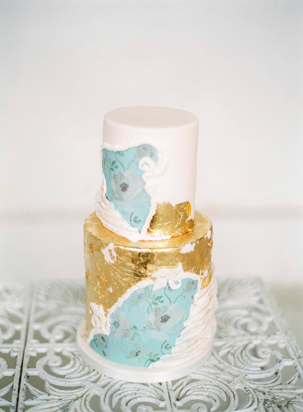 gold leaf wedding cake with blue paint