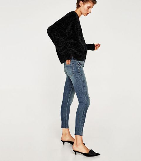 With loose shirt and skinny jeans