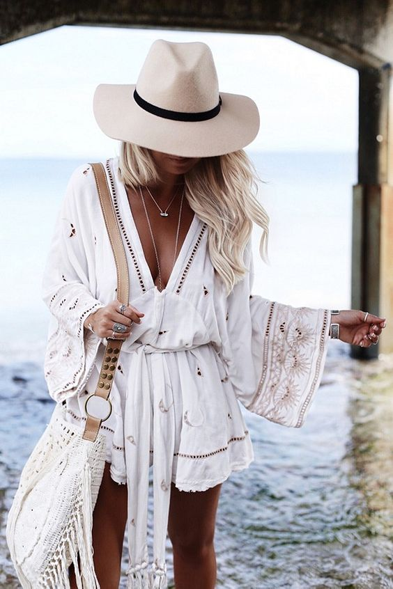 a boho white beach romper with lace detailing and embroidery plus a plunging neckline