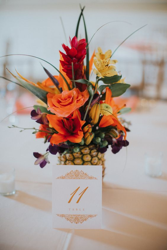 a pineapple wedding centerpiece wih orange, red and yellow blooms and some greenery