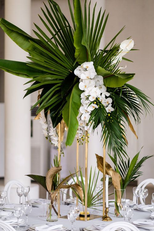 a glam tropical centerpiece of large tropical leaves and white orchids on tall gilded stands