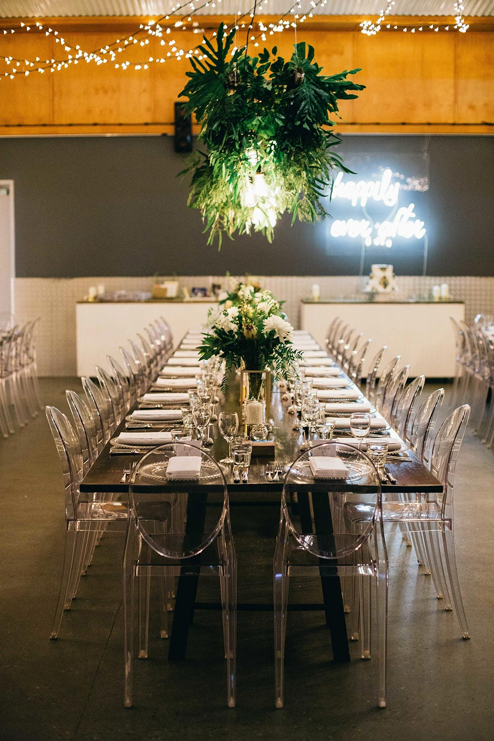 industrial wedding reception with suspended greenery, neon signage and lucite chairs