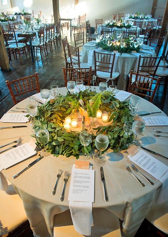 a greenery table centerpiece with eucalyptus, ferns and candles is a unique wreath-like piece