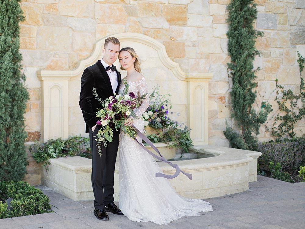 long sleeve embellished wedding dress and black velvet groom tux with purple flower bouquet