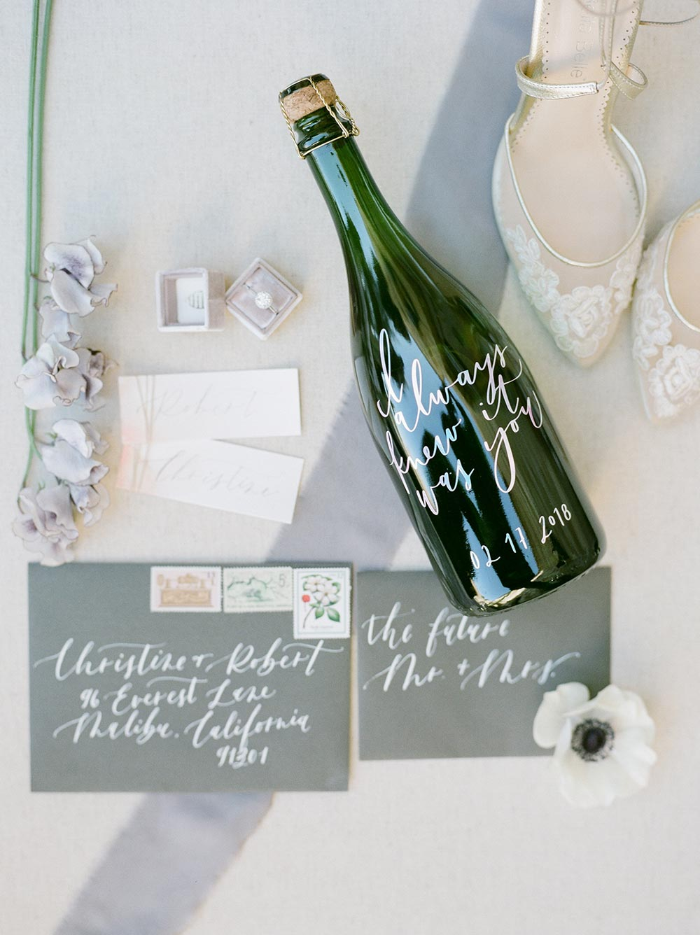 calligraphed wedding stationery and personalized champagne bottle