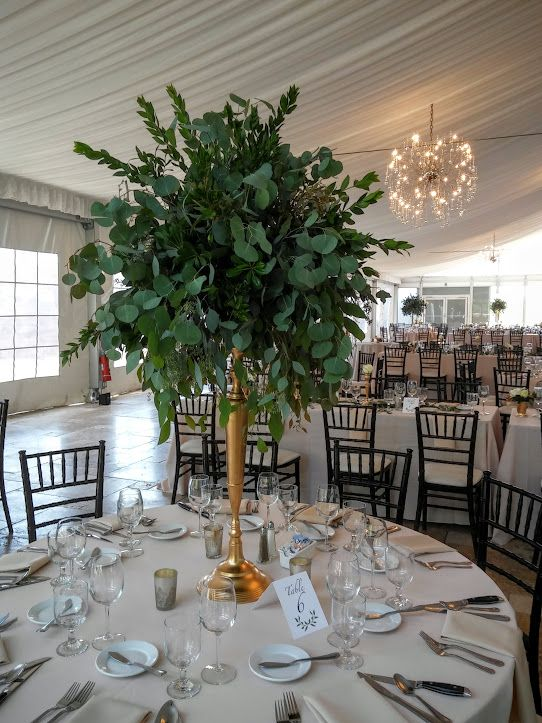 a tall greenery wedding centerpiece shaped as a ball on a tall gilded stand