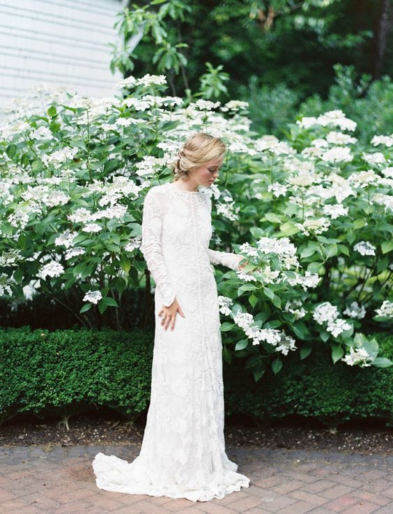 a lace sheath wedding dress with long sleeves, a high neckline, a small train and buttons for a modest look
