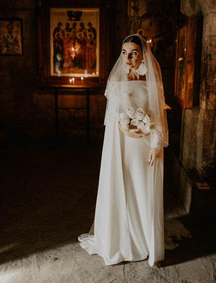The bride was wearing an amazing modern off the shoulder dress with long sleeves, a layered veil and statement earrings