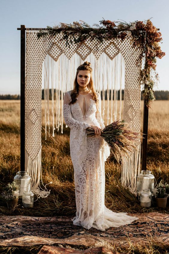 a boho lace wedding dress with a cutout neckline, long bell sleeves and a train