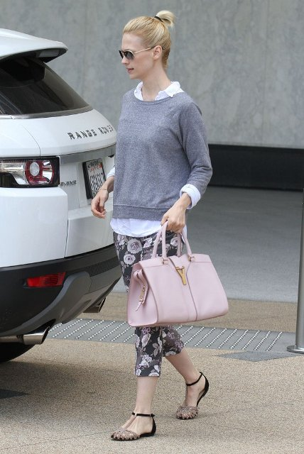 With floral pants, white shirt, gray sweatshirt and pale pink bag