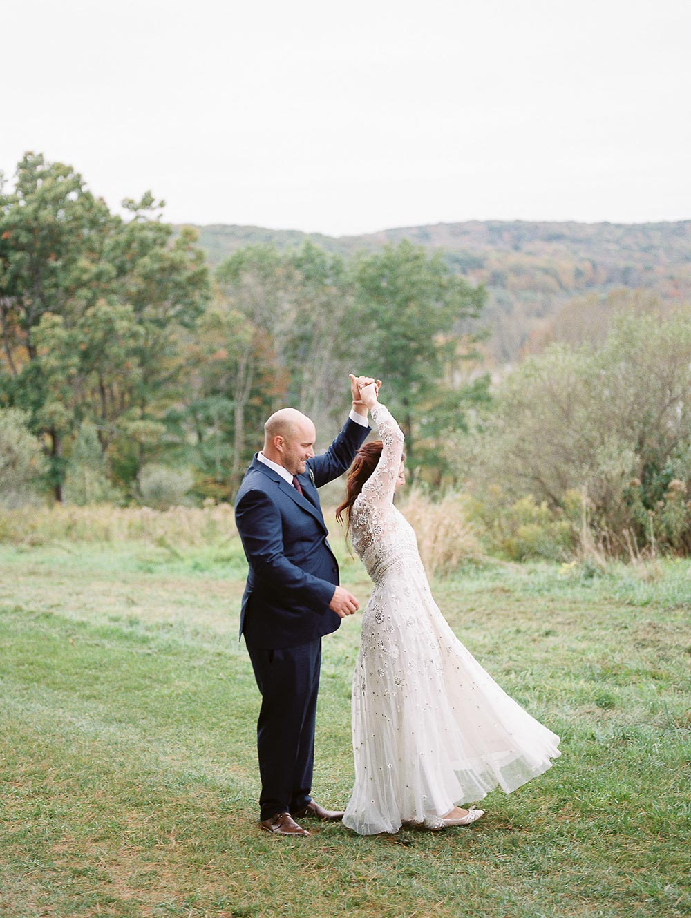 embellished long sleeve wedding dress and navy groom suit