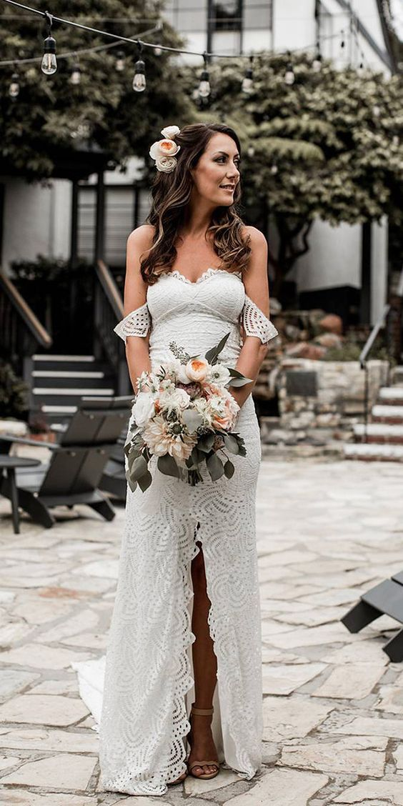 an off the shoulder sheath wedding dress with a sweetheart neckline, a front slit and a train