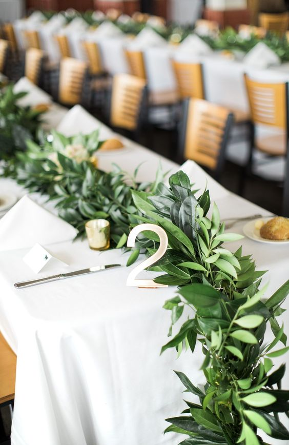 a lush and textural greenery table runner with small candles in candle holders is a cute idea