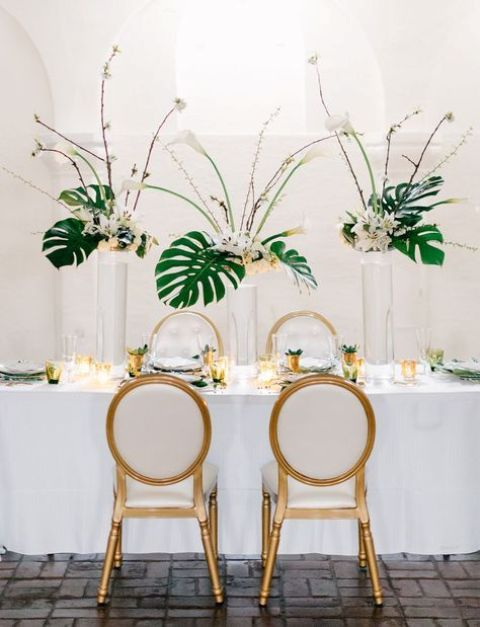 gorgeous tropical centerpieces with tropical blooms and palm leaves for a glam or art deco wedding